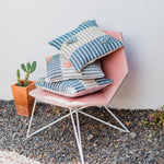 A stack of colorful, vibrant organic cotton pillows handmade by Colombia and inspired by a rural village there are stacked above a beautiful architectural and modern chair, sitting next to a cactus potted in a terracotta pot.