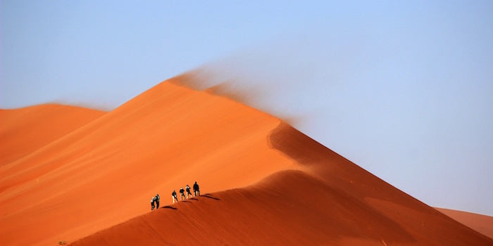 People climbing to the top of a sand dune