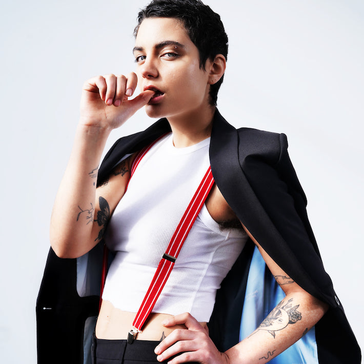 Model with short brown hair, wearing white tank top, red suspenders, and black blazer worn over their shoulders, staring at the camera
