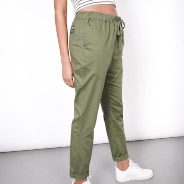 Waist down shot of model in olive colored essential pant with drawstring waistband and white sneakers