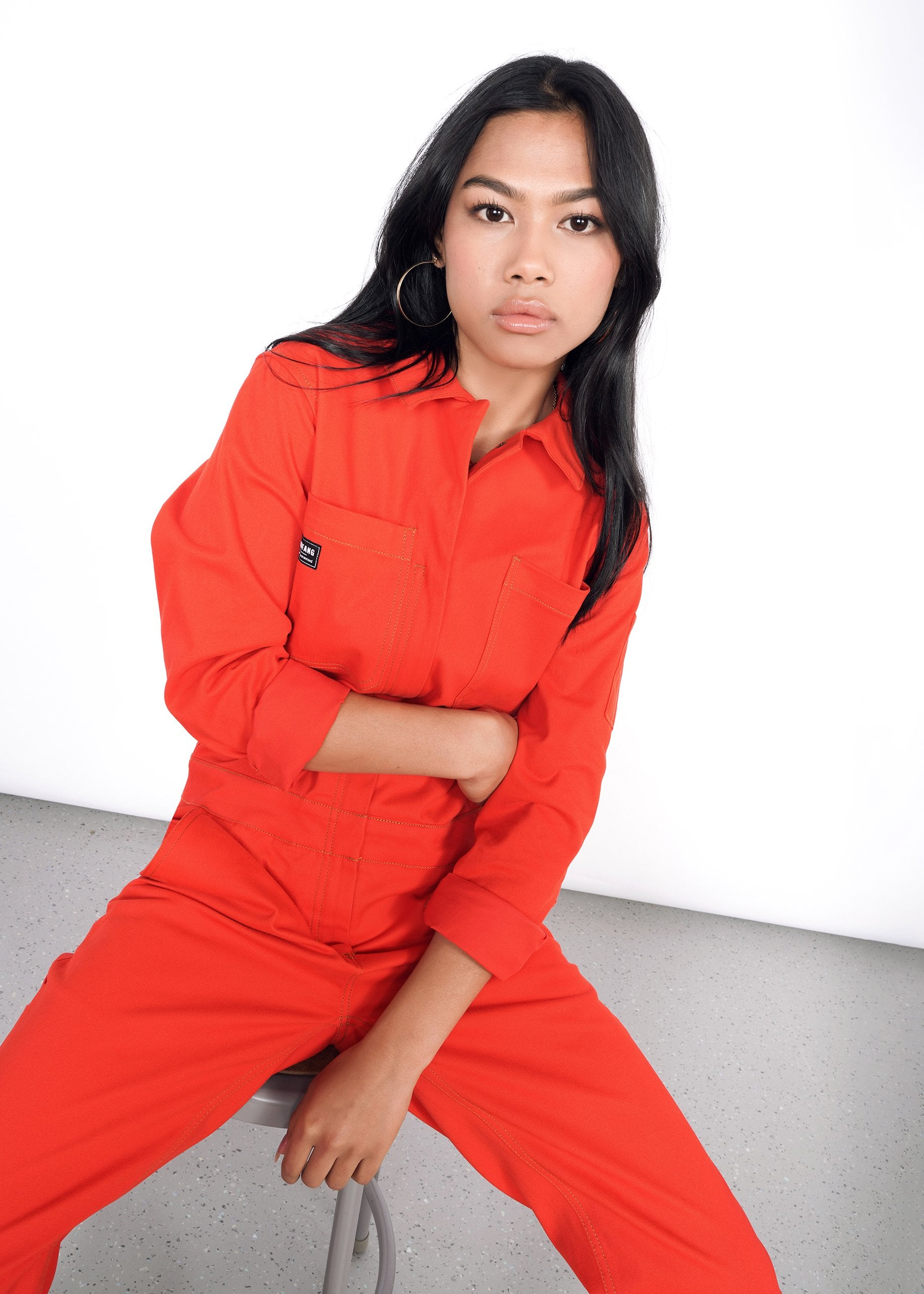 Image of model sitting on stool wearing bright red long sleeve coveralls