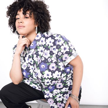 Model with curly hair, sitting, wearing purple and white floral printed button up shirt and black pants