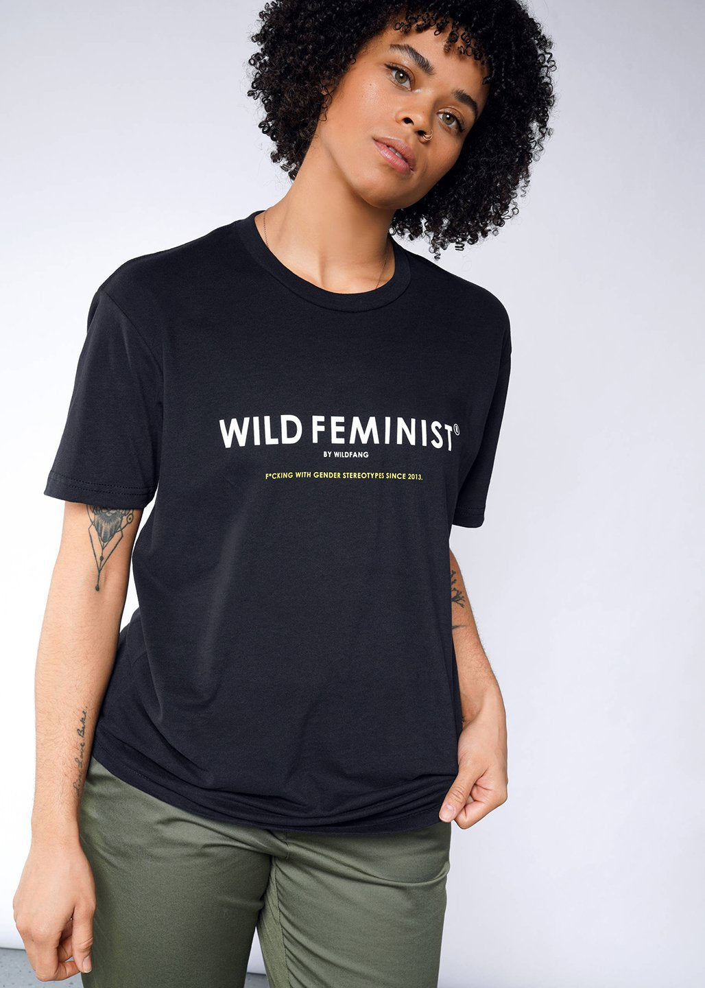 Image of model wearing Wild Feminist tee in gray with white text
