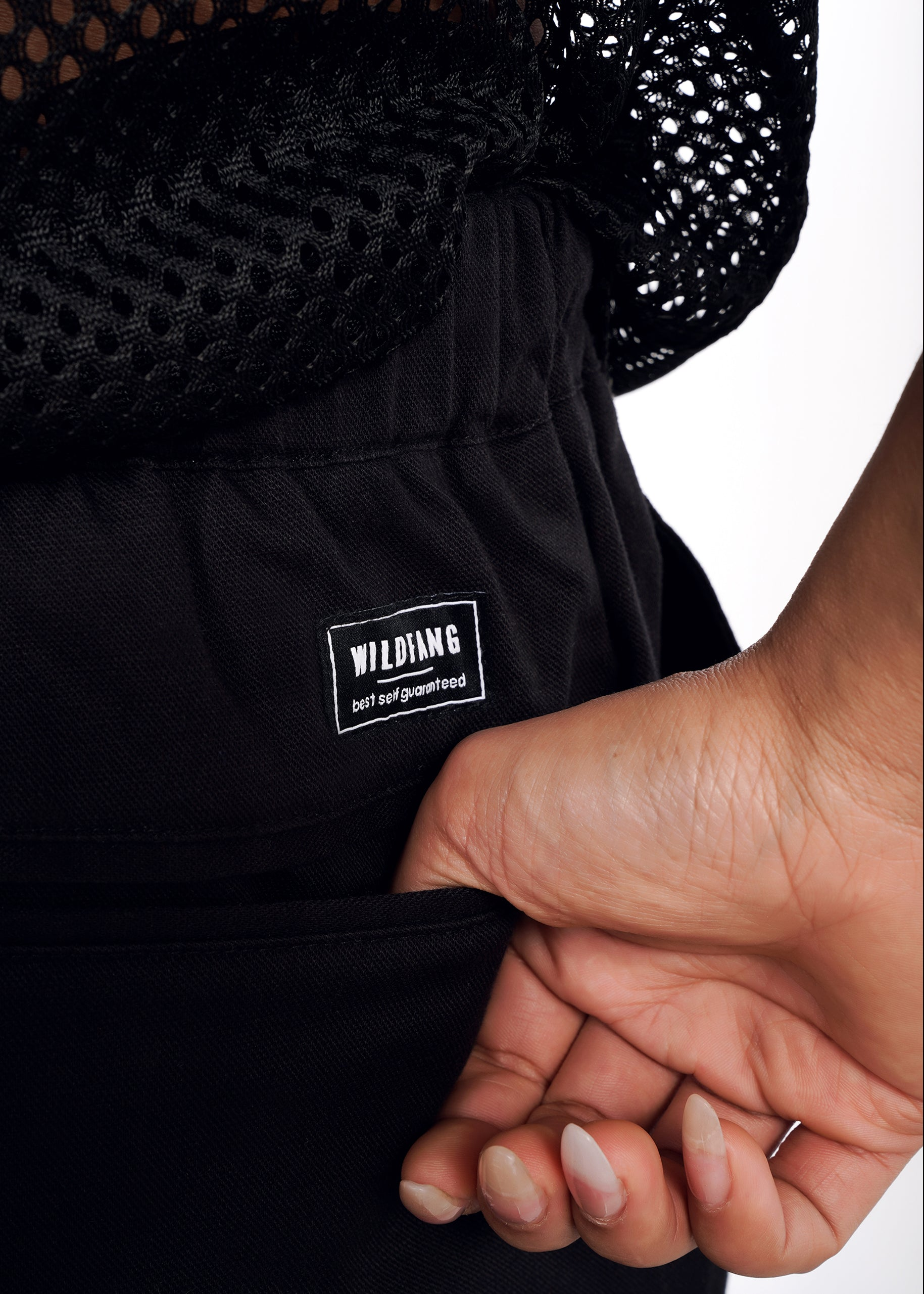 "Detail shot of hand in back pants pocket, with mesh top and patch that reads ""WILDFANG 