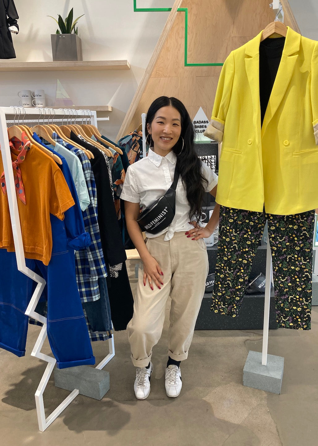 Image of store associate in store next to a clothing rack and yellow blazer hung up