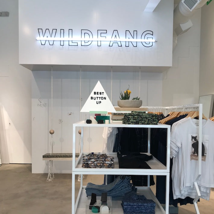 Inside the Wildfang retail store, a clothing rack with folded clothes and triangle shaped sign, swings, and WILDFANG neon sign on back wall