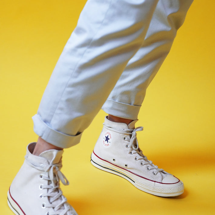 Close up of light gray trousers and white converse with a yellow background
