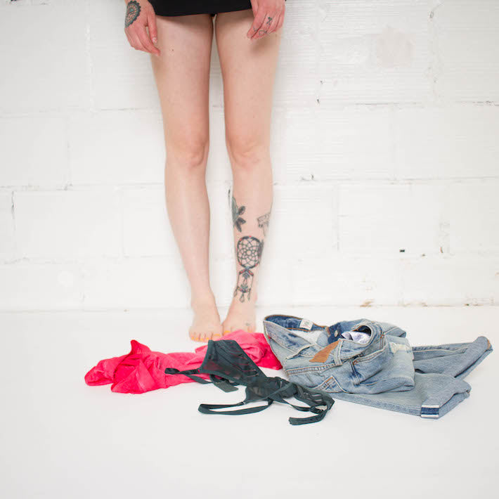 Waist down person standing with bare legs with tattoos on one and tattoos on hands. Jeans, bra, and shirt piled on the floor below.