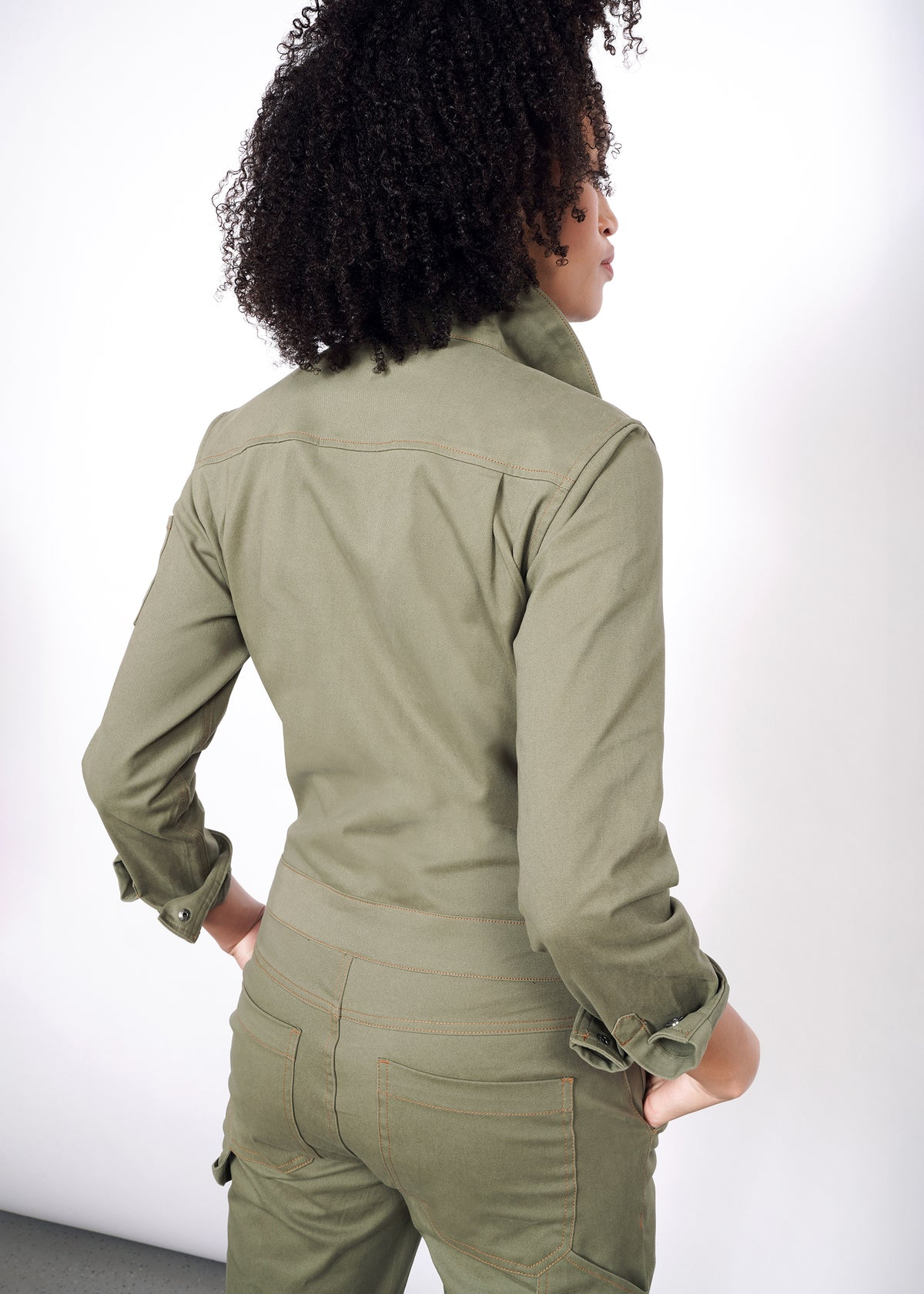 Back of olive coveralls modeled in size small, with sleeves cuffed once