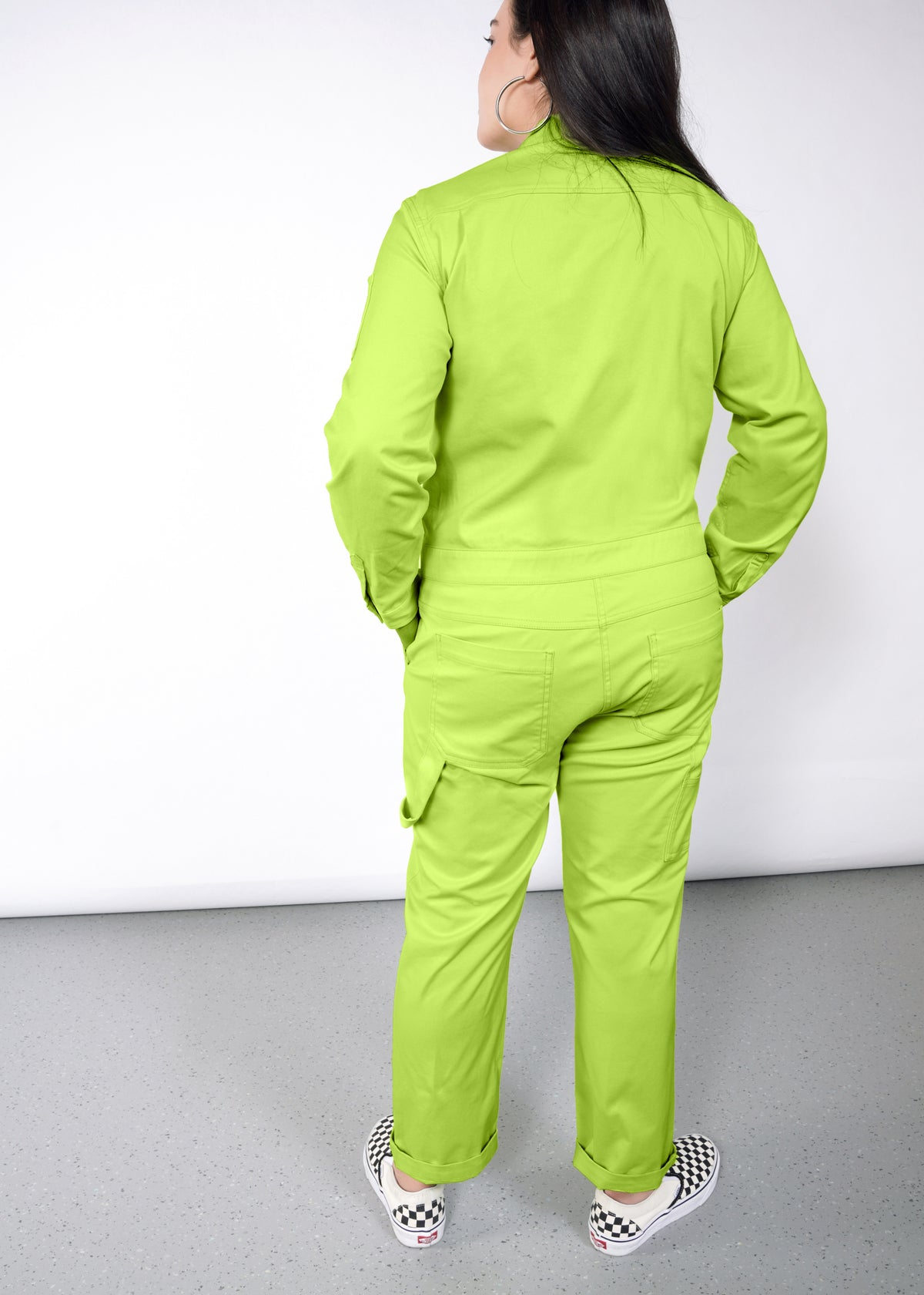 Model wearing neon green long sleeved essential coverall jumpsuit in size large, hands in pockets, turned away
