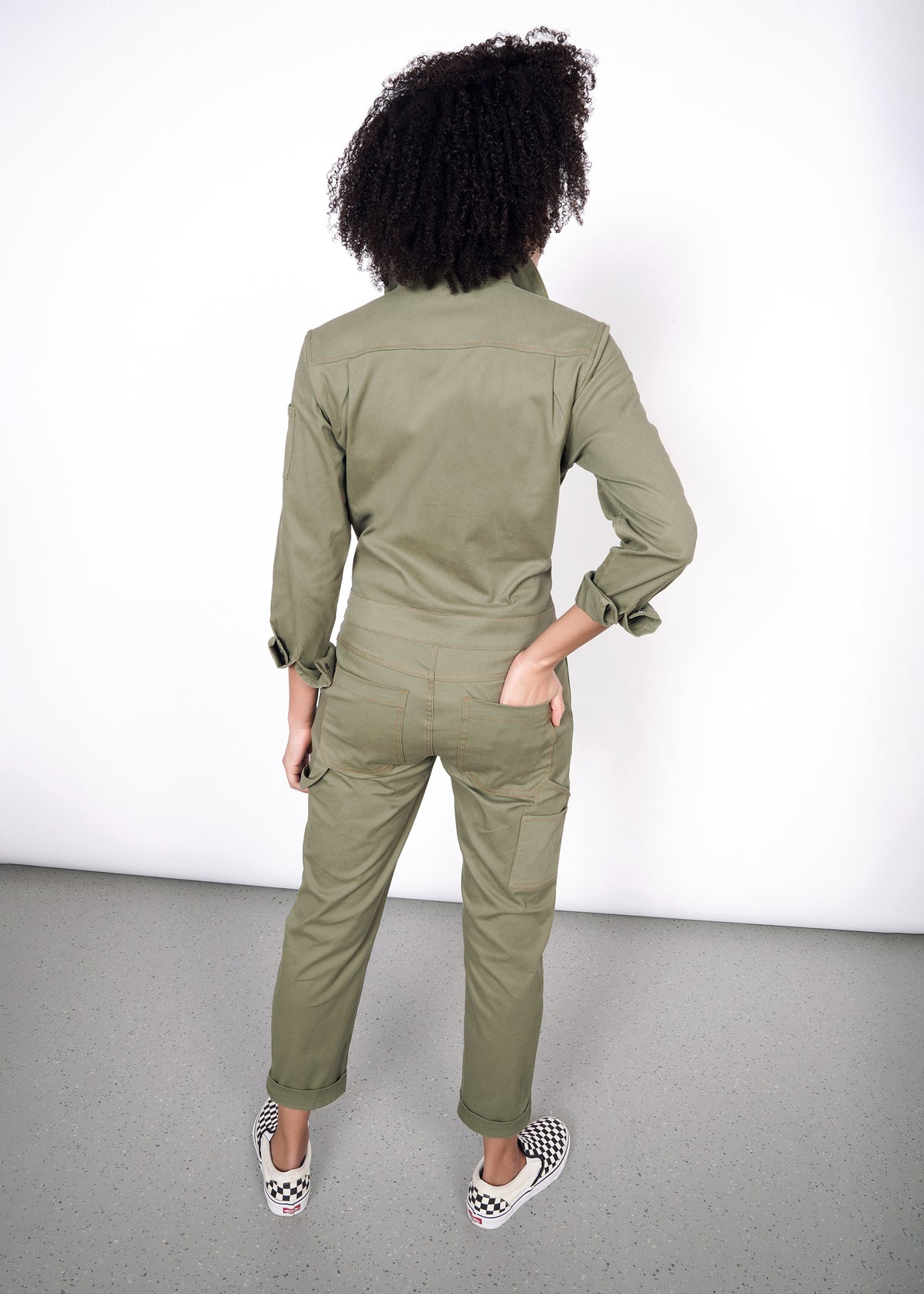 Model wearing size small olive coveralls, showing back of garment, one hand in right back pocket