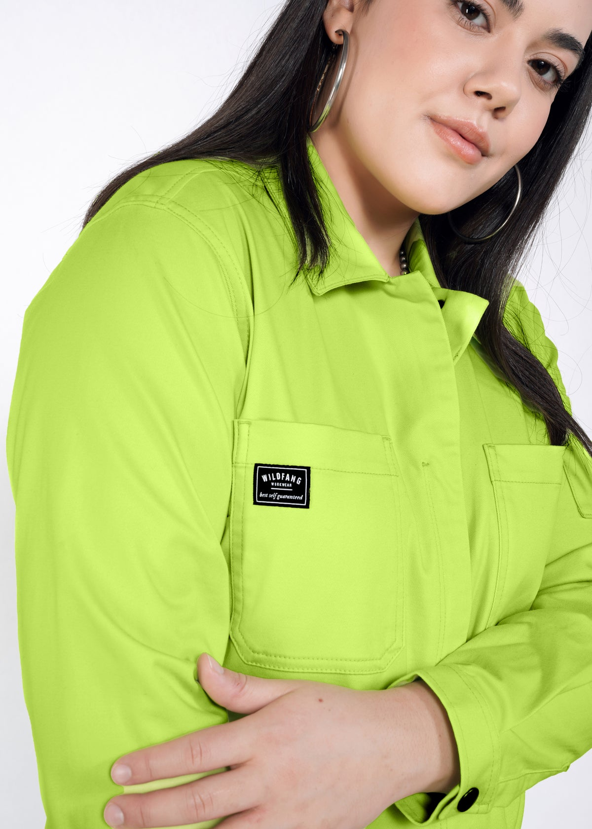 "Model wearing neon green long sleeved essential coverall jumpsuit in size large, showing detail patch on front chest pocket that reads ""WILDFANG WORKWEAR 