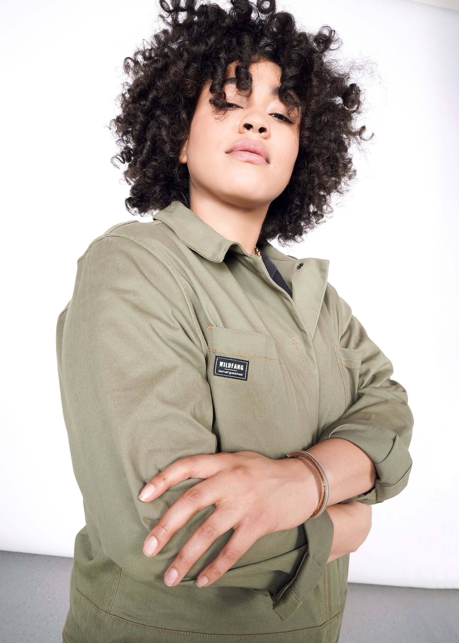 Curly haired model wearing olive long sleeve coveralls with arms folded at chest