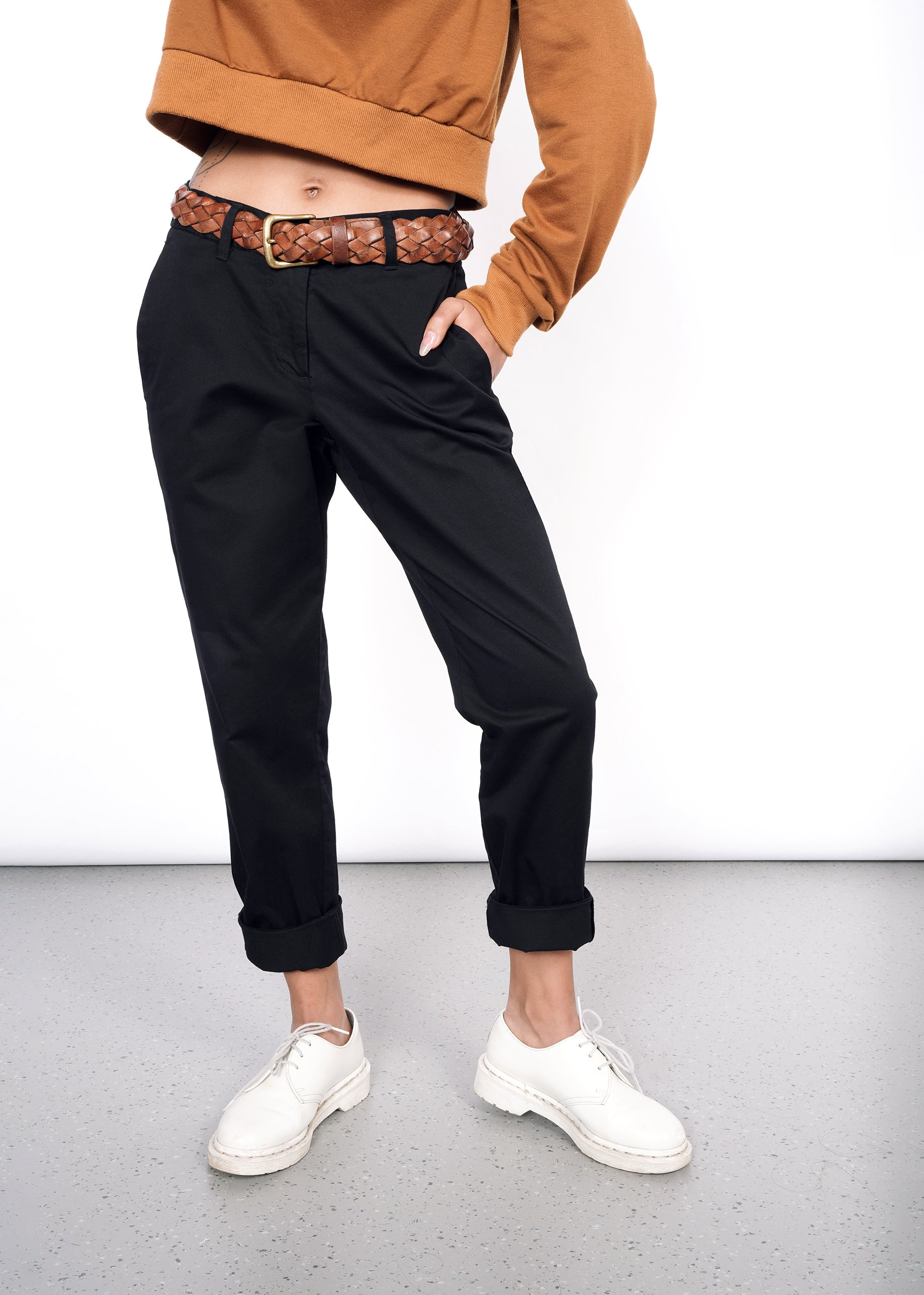 Model wearing black essential trouser pant in size 2, with hand in pocket and pant legs cuffed up