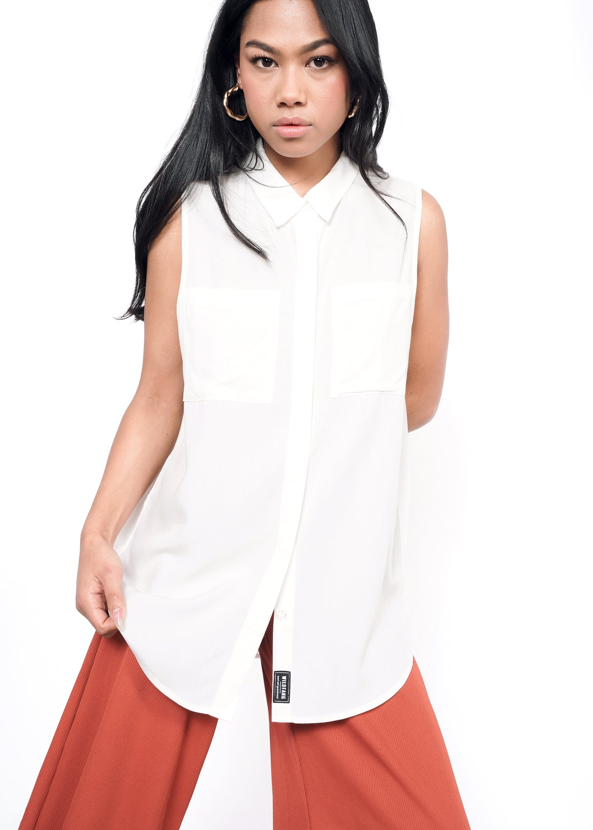 Model wearing white sleeveless drapey button up shirt in size XS, with orange pants