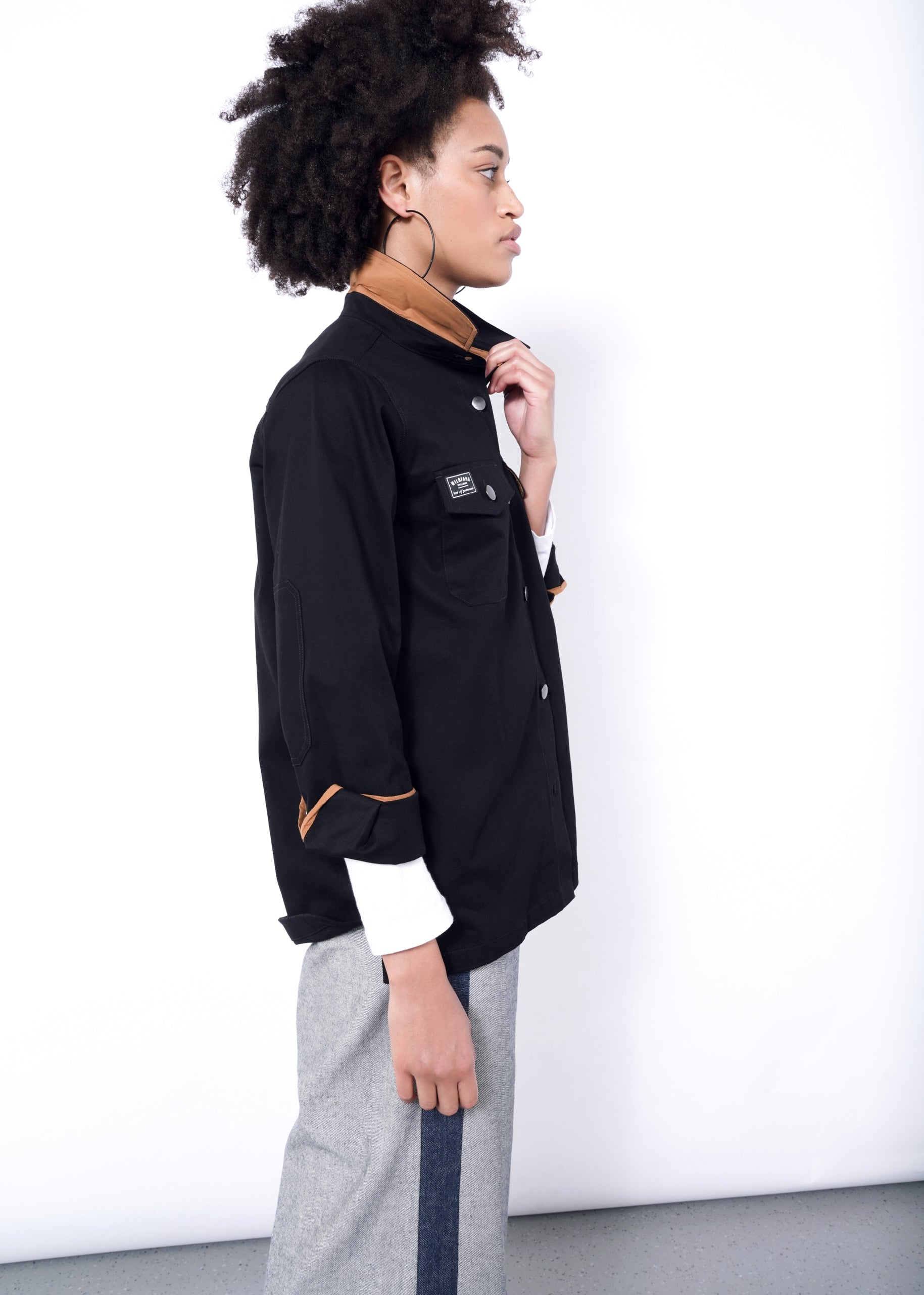 Model facing right, wearing black essential shirt jacket (shacket) in size medium with collar popped to show orange contrast lining