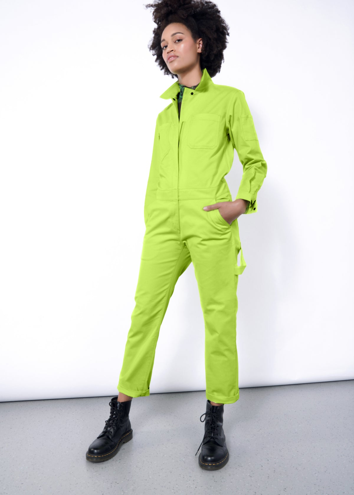 Model wearing neon green long sleeved essential coverall jumpsuit in size small, with hand in pocket