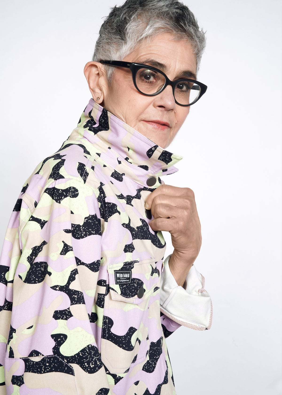 Model with gray short hair and glasses wears lavender, celadon, and black camouflage all over print shirt jacket (shacket) in size small