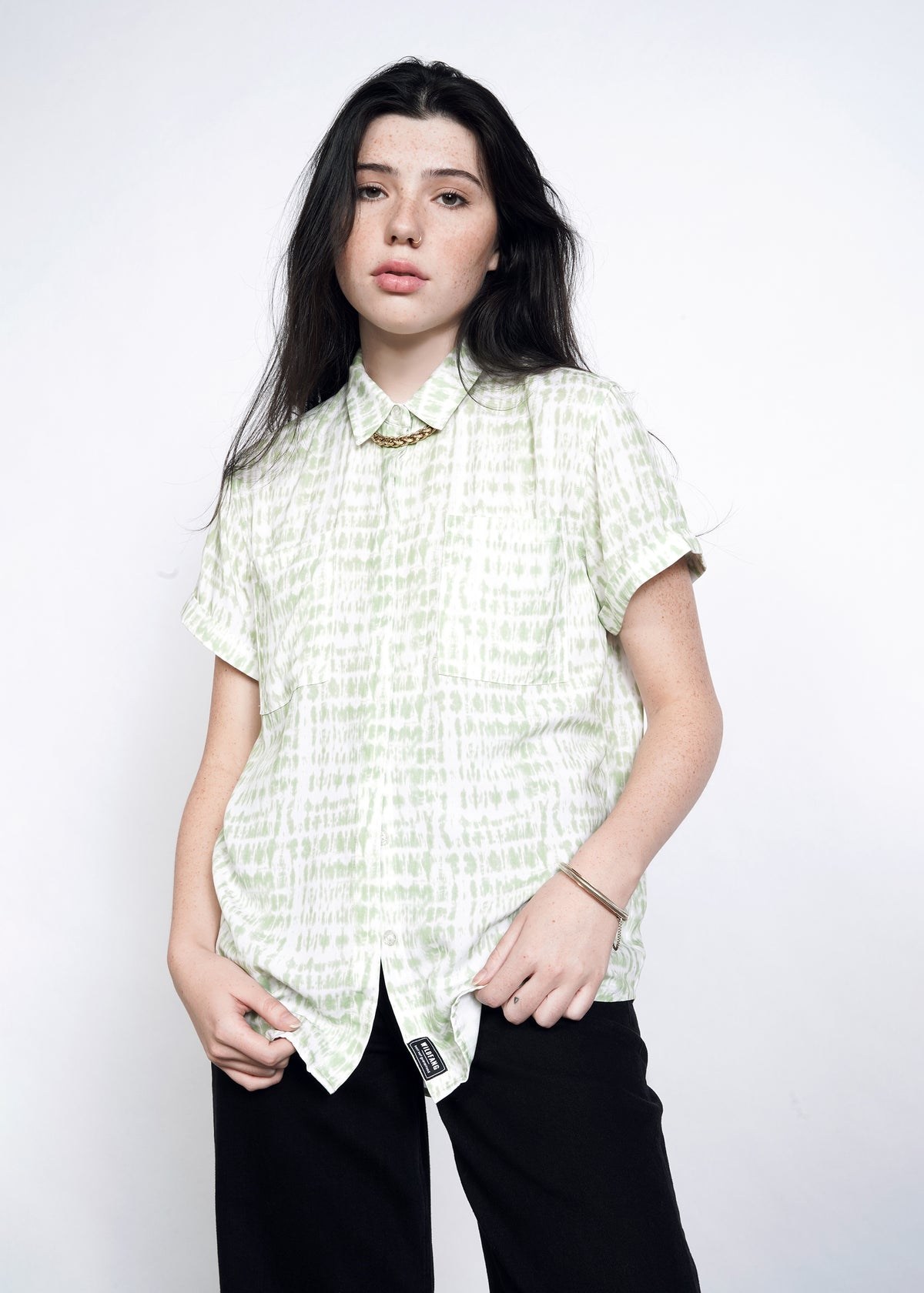 Model wearing celadon green shabori print loose fit button up, buttoned all the way to the top