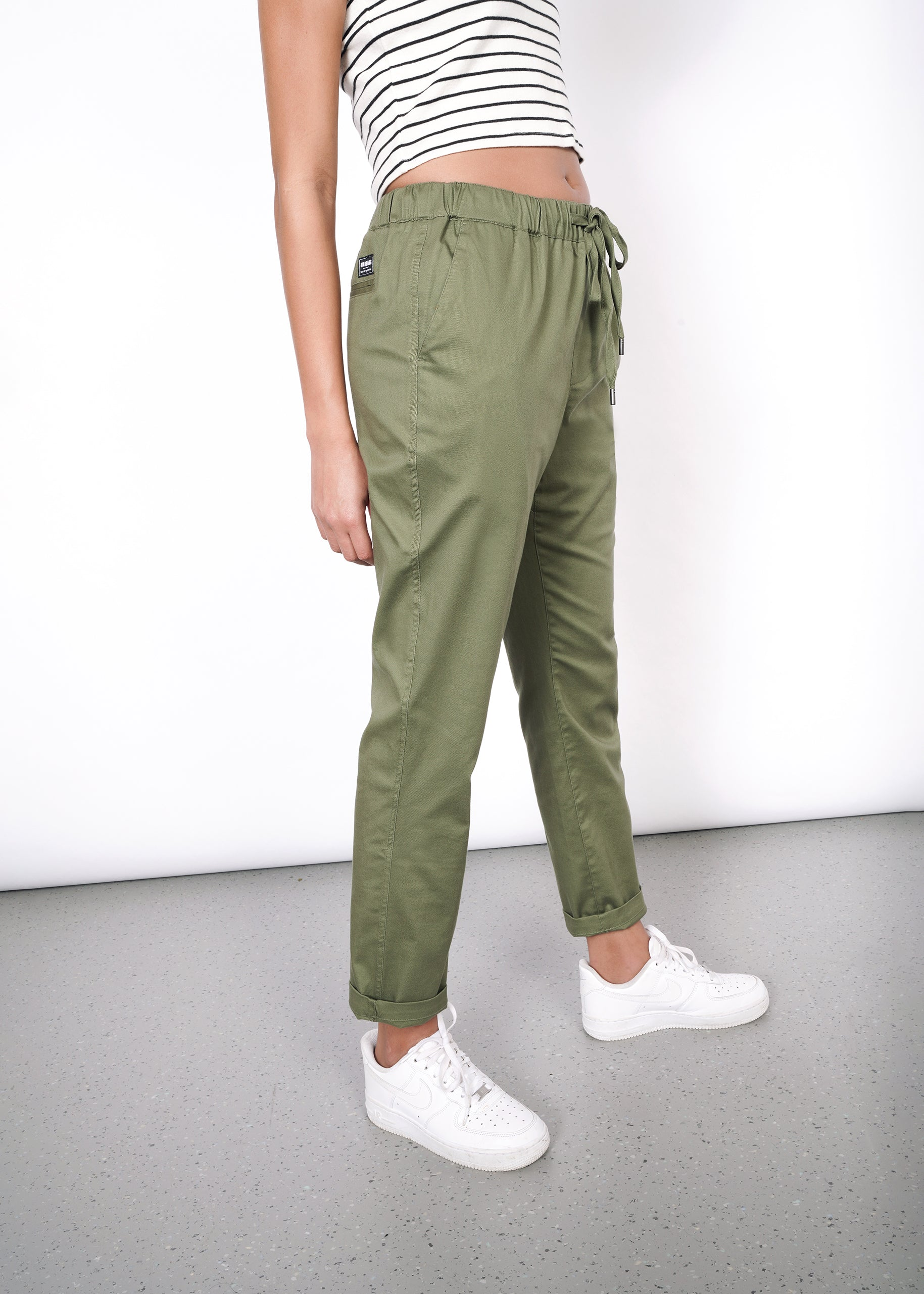 Olive drawstring pant on model, styled with white Nike sneakers and white striped tank top