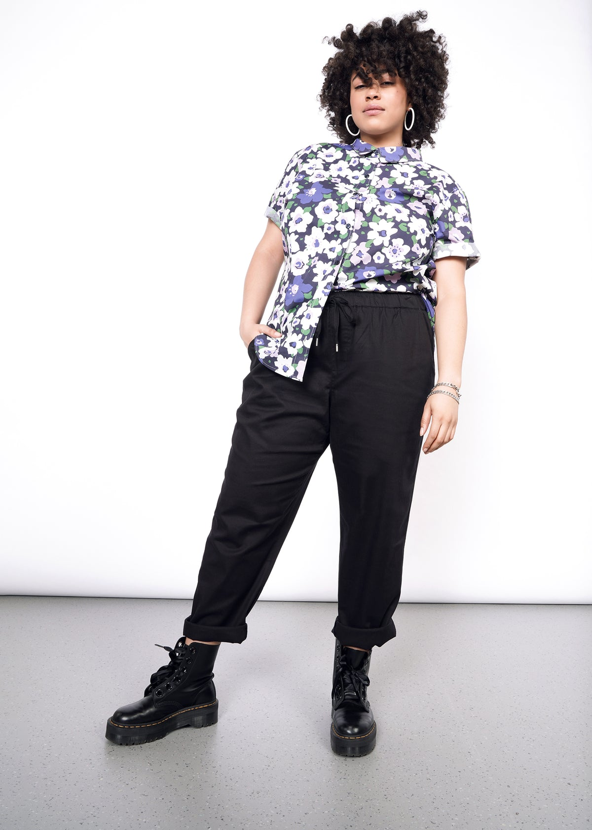 Black drawstring pant styled with floral button up shirt and black boots.