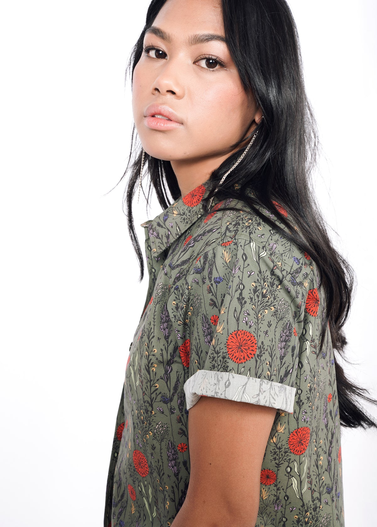 Model wearing botanical all over printed short sleeved button up shirt in size XS, with the sleeves cuffed