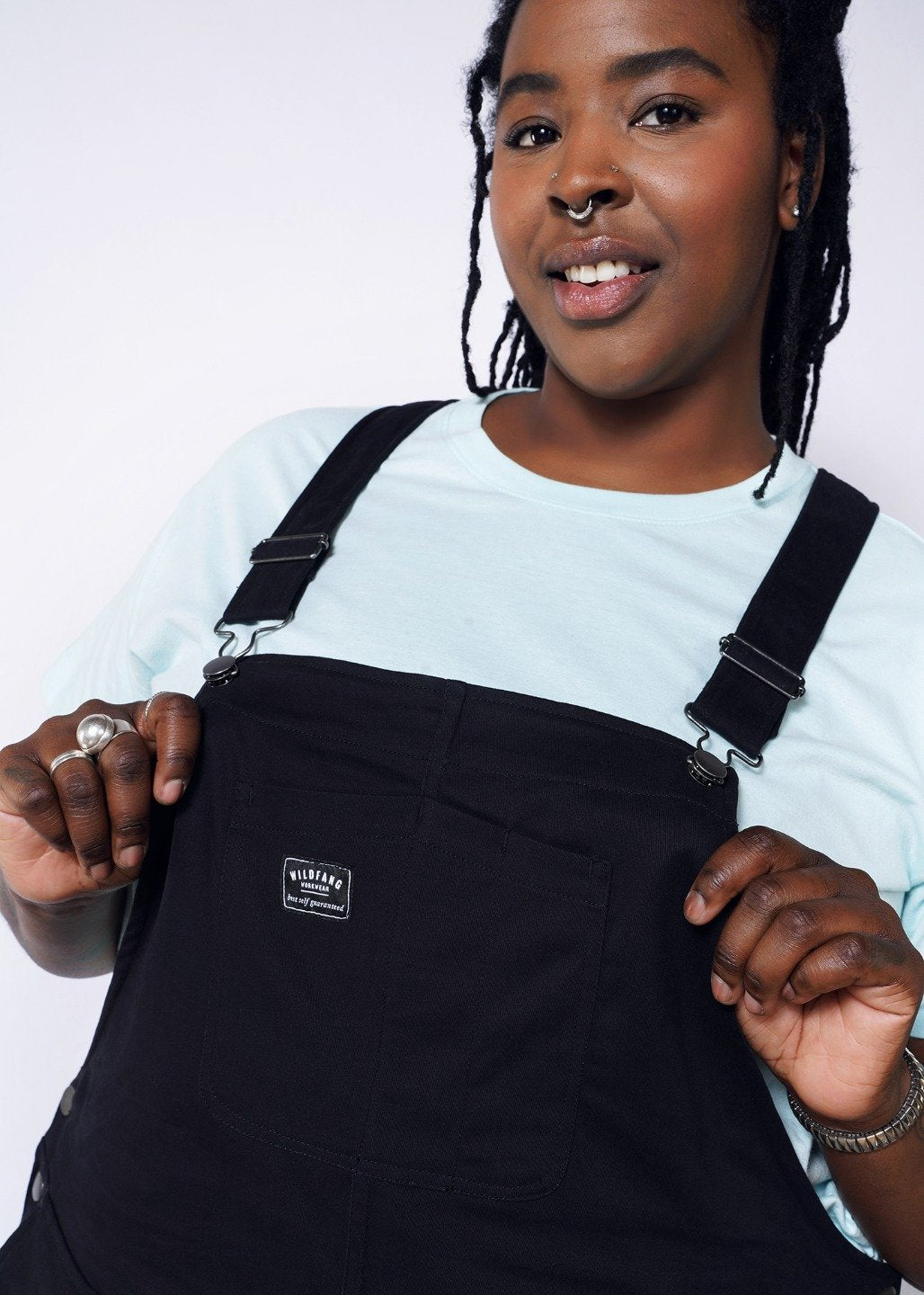 Model wearing black overalls with metal hardware in size XXL, with an blue tee underneath, holding front bib