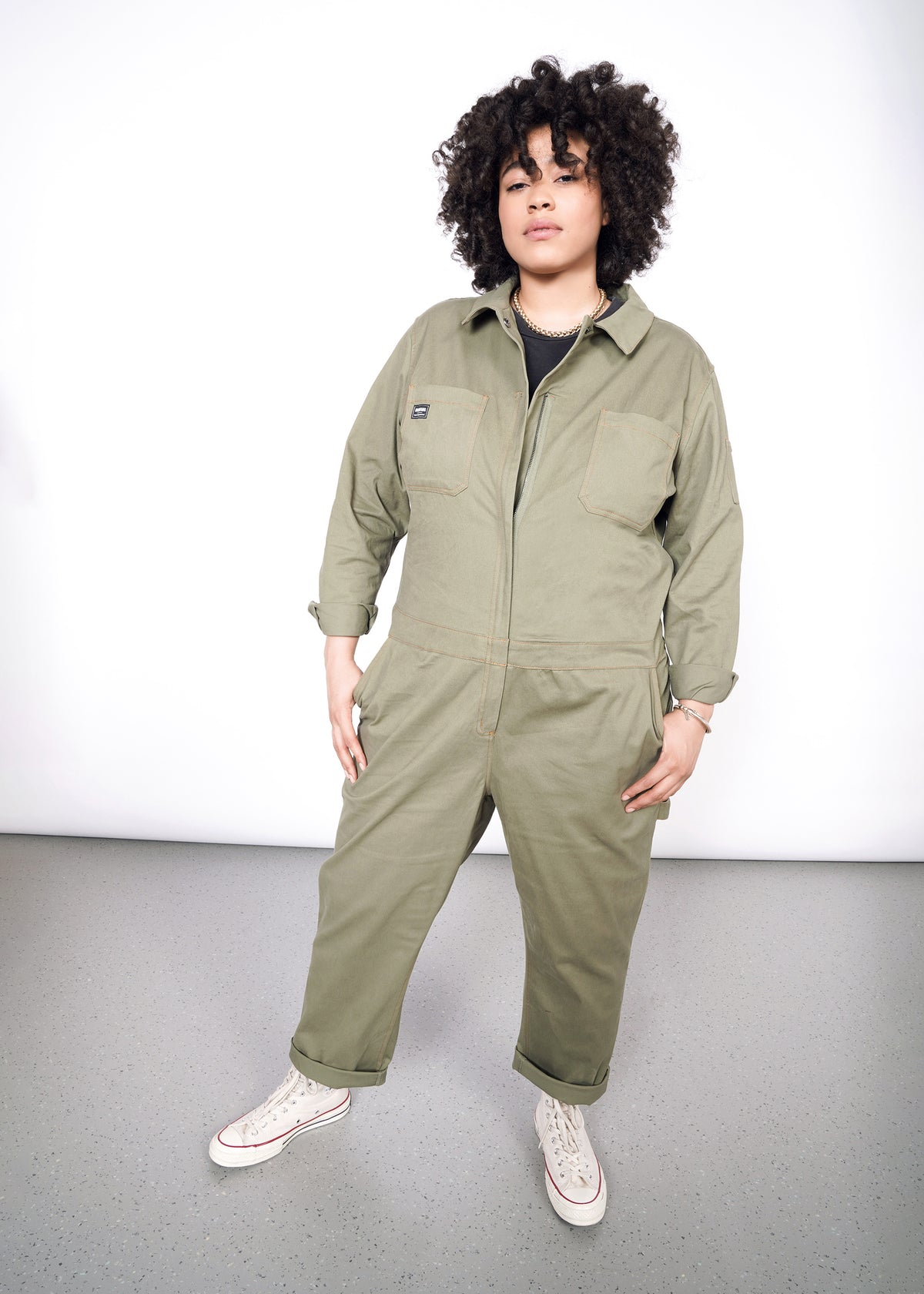 Tambrie is wearing the olive long sleeved coveralls in size XXL, with a gray tee and white converse