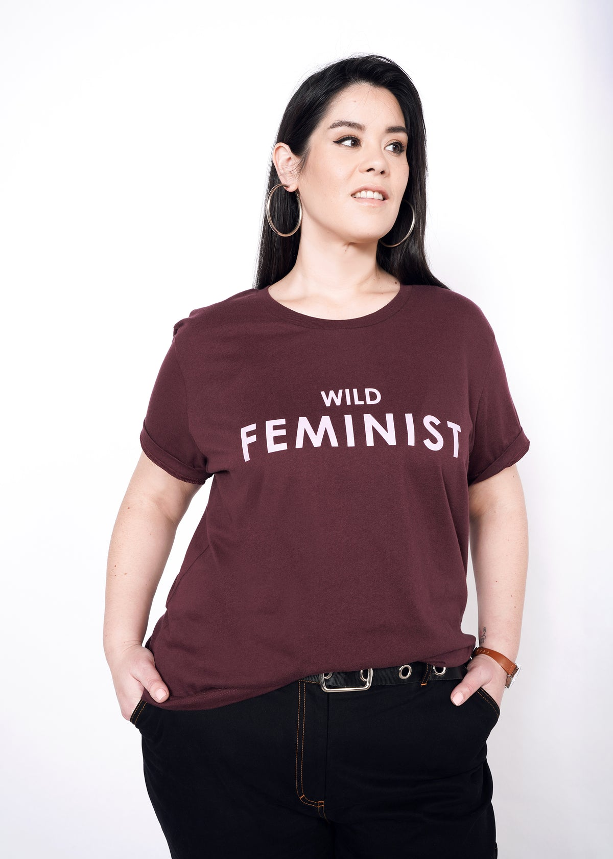 "Model standing with hands in pockets, wearing burgundy merlot graphic tee in size XXL that reads ""WILD FEMINIST"" in light lavender"
