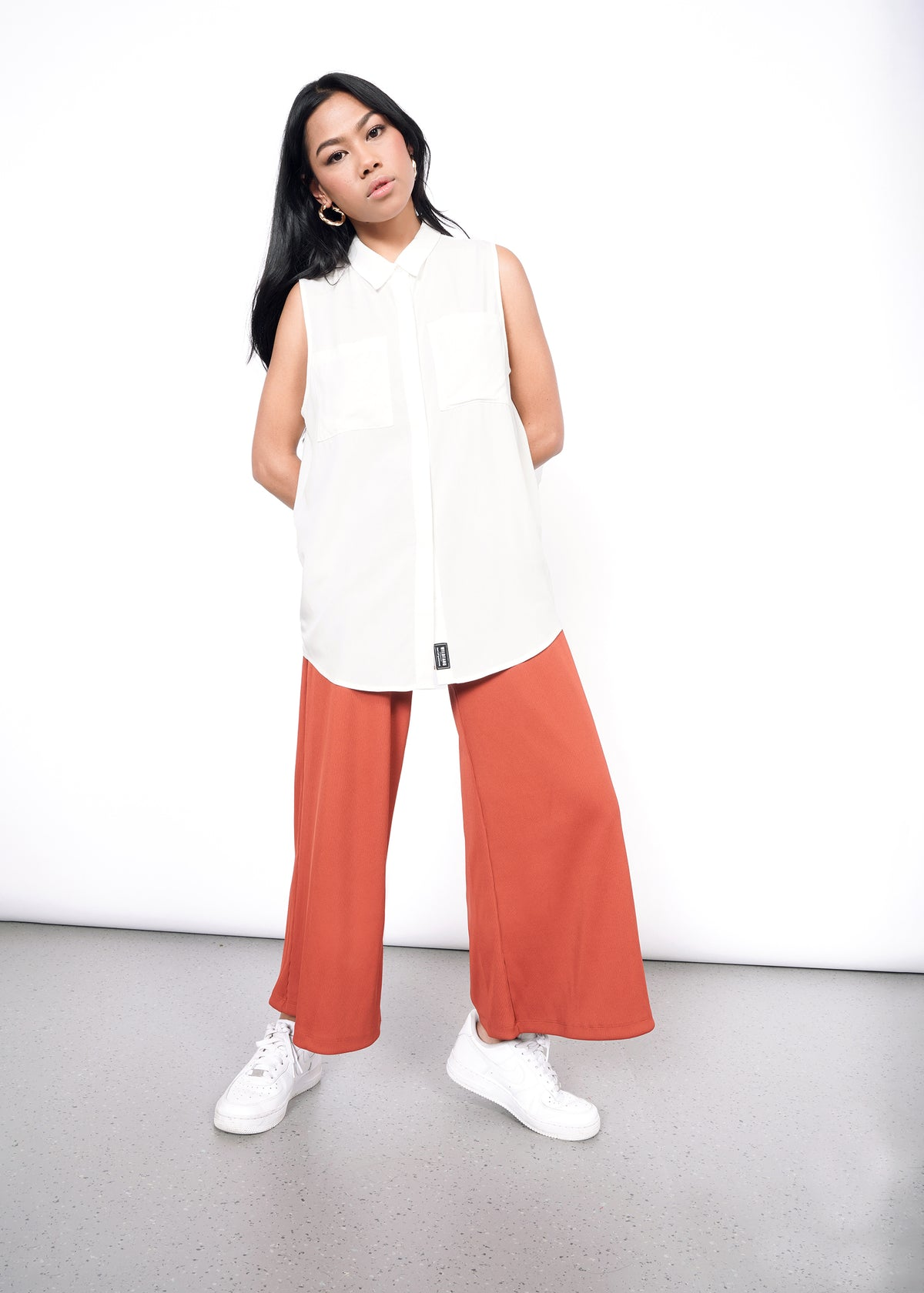 Model wearing white sleeveless drapey button up shirt in size XS, with orange pants and white sneakers