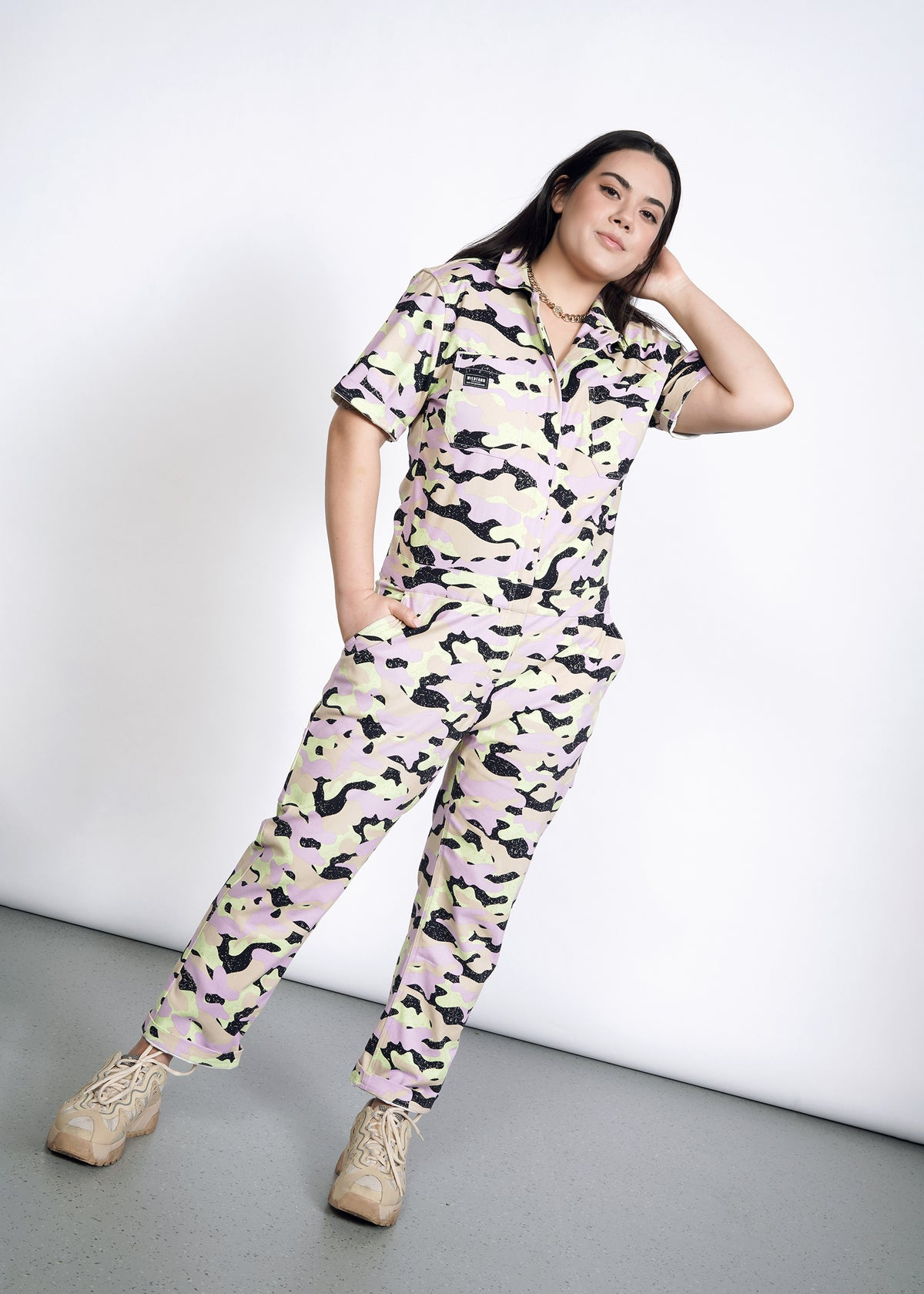 Model wearing lavender, celadon, black, and tan camouflage all over print short sleeve coverall jumpsuit in size L, standing with one hand in pocket