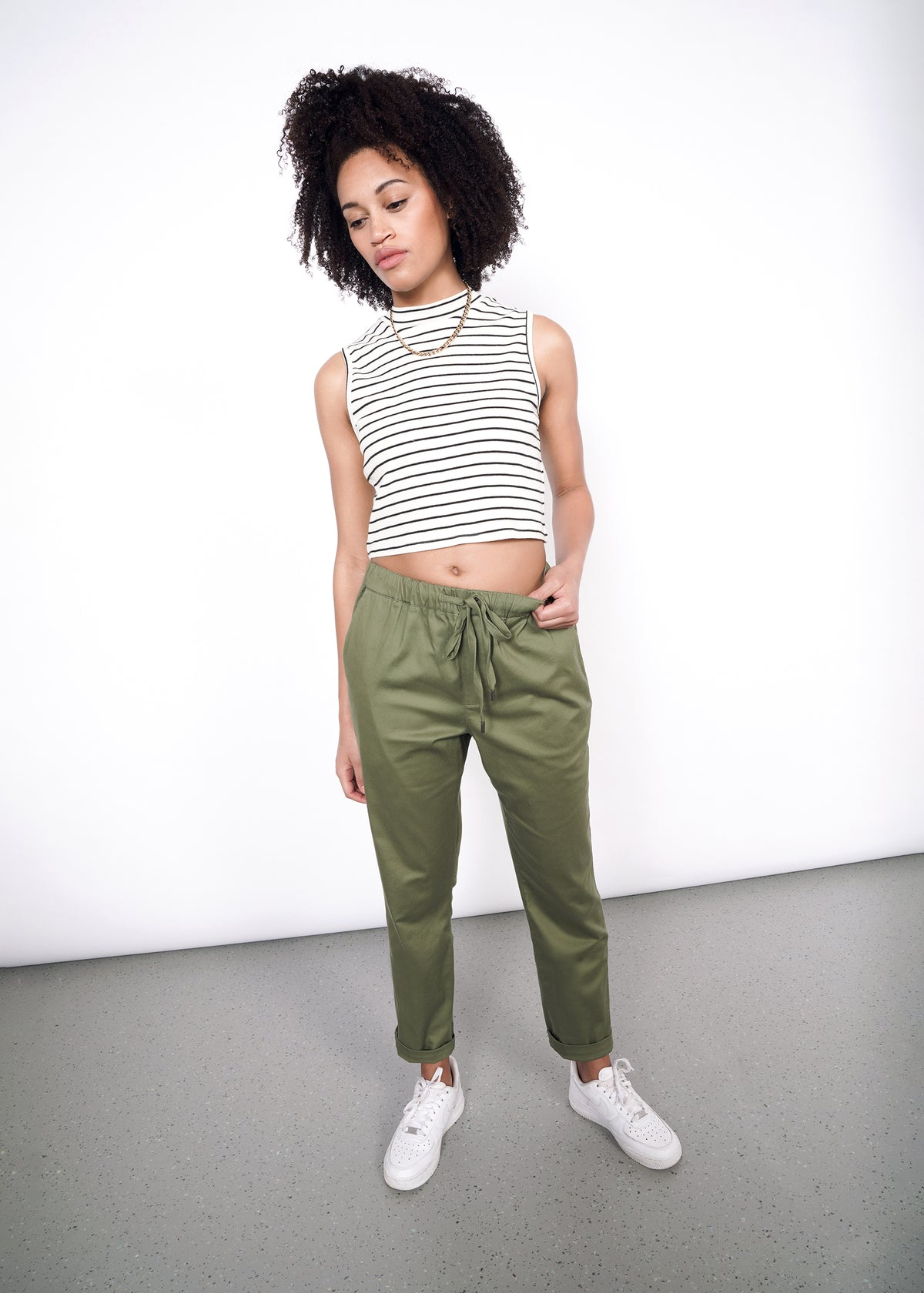 Model with curly hair wearing olive drawstring pants, white sneakers, and white tank top with black strips.