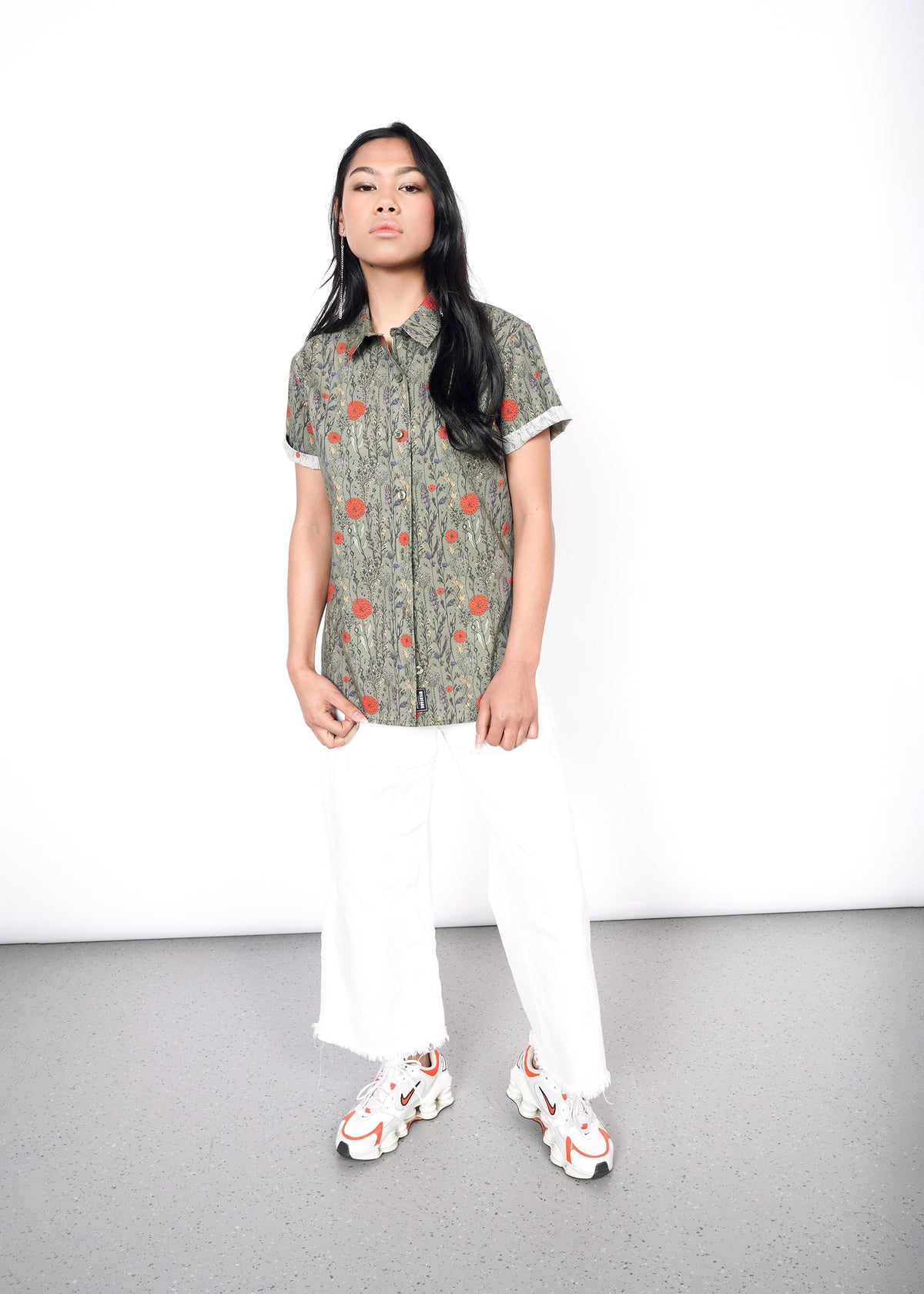 Model wearing botanical all over printed short sleeved button up shirt in size XS, with the sleeves cuffed, untucked, and with white pants