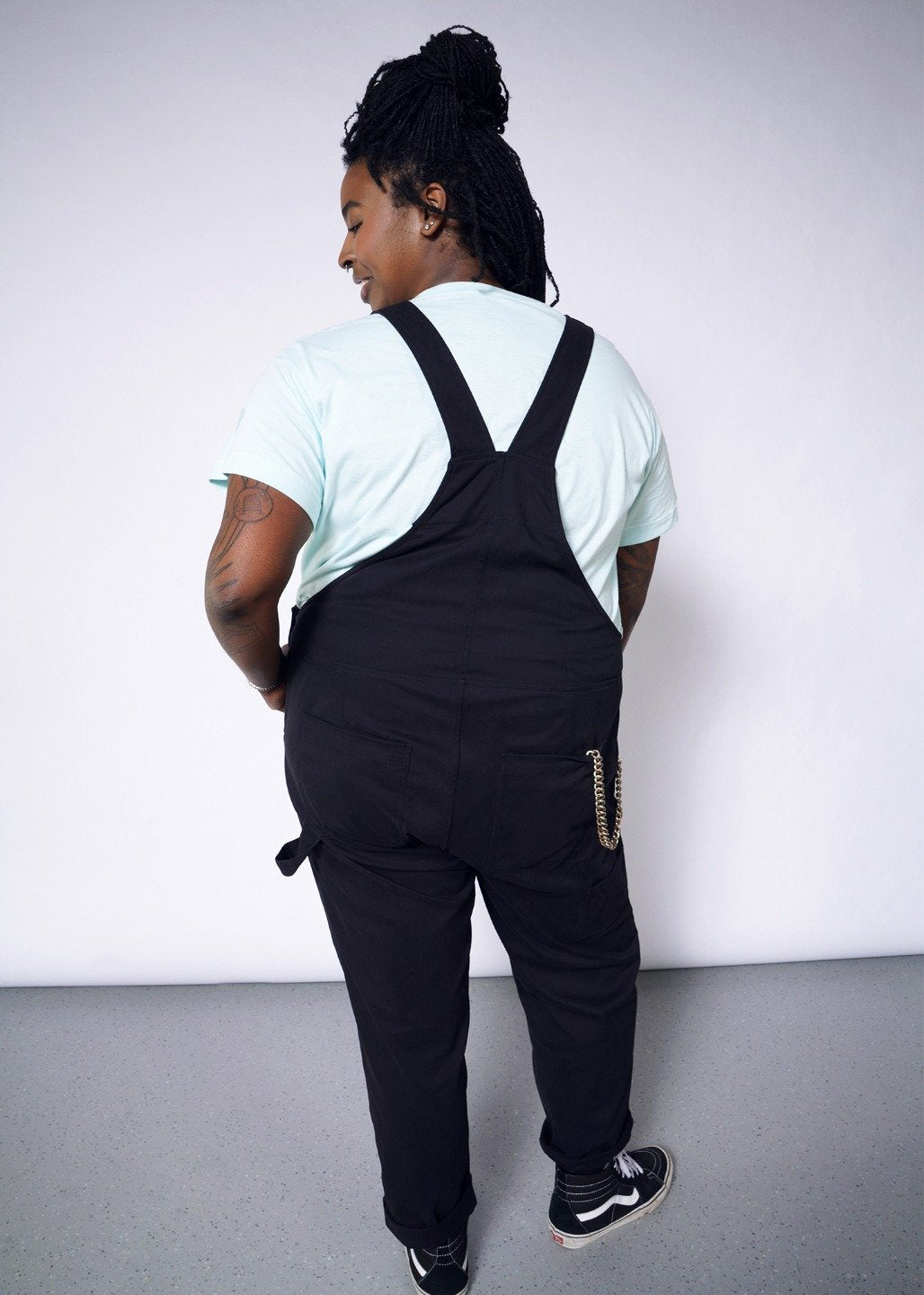 Backside of model wearing black overalls with metal hardware in size XXL, with an blue tee underneath and chain in back pocket