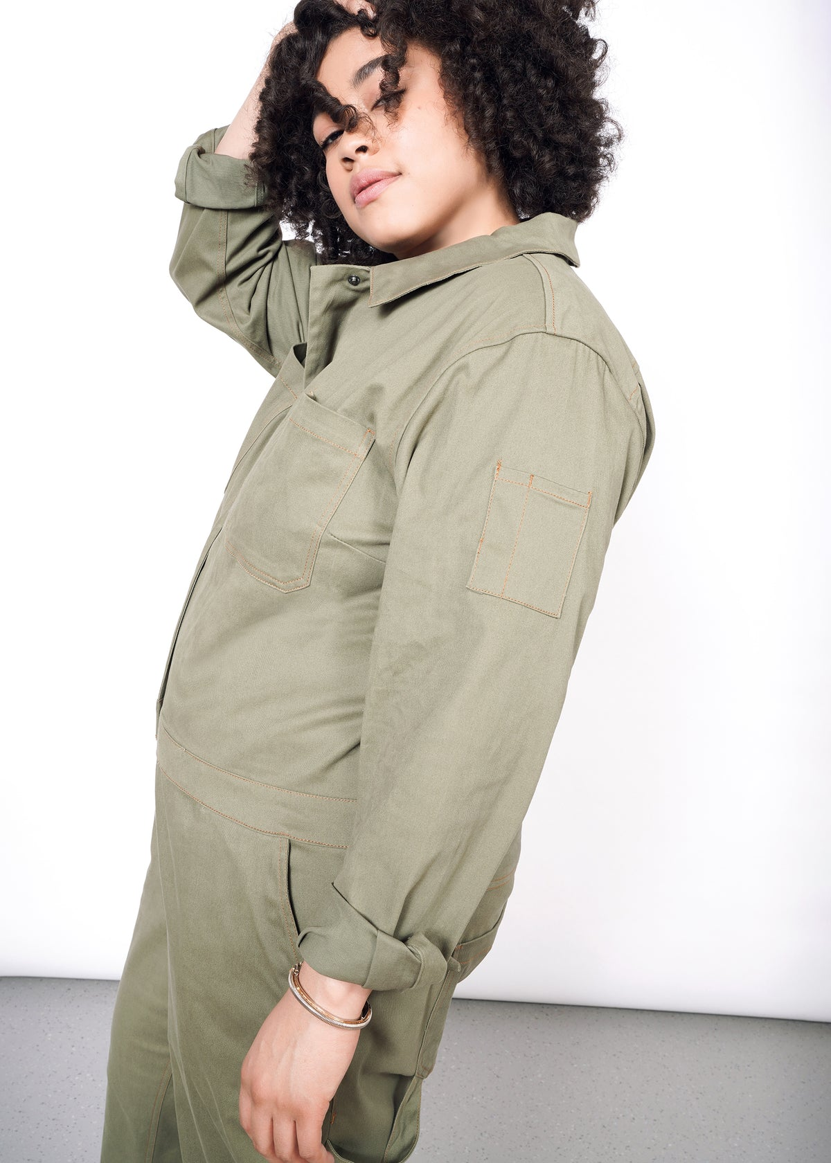 Profile view of curly haired model wearing olive long sleeve coveralls, showing the pocked and orange stitching on sleeve