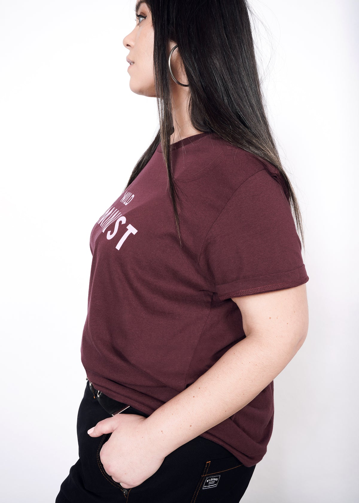 Side view of model wearing burgundy merlot graphic tee in size XXL with hands in pockets, sleeves folded up once