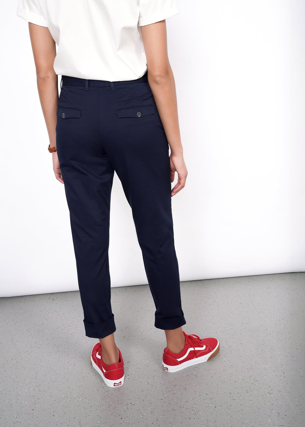 Backside of model wearing mid rise tailored trouser in navy size 4, cuffed, with white button up tucked in, and two back button pockets