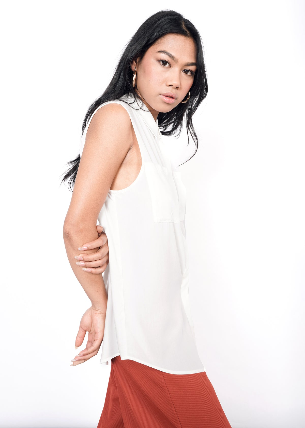 Model wearing white sleeveless drapey button up shirt in size XS, with orange pants and arms behind back