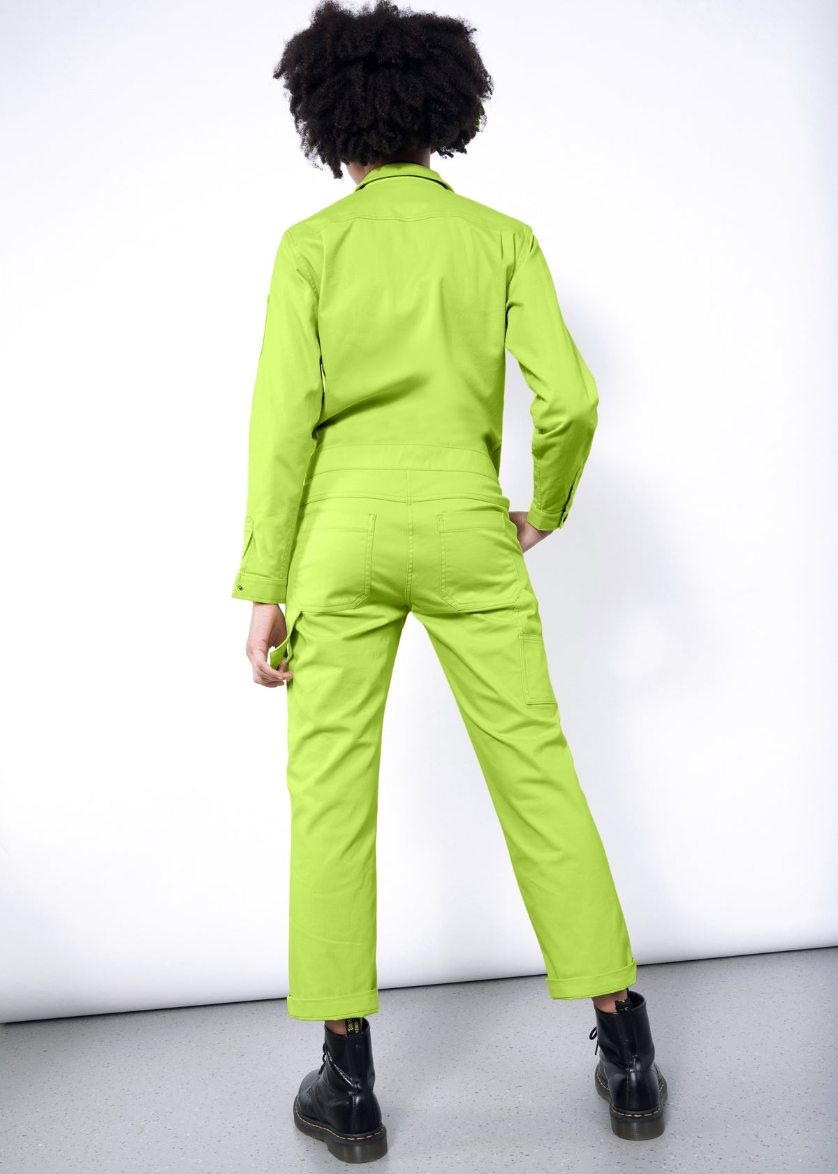 Model wearing neon green long sleeved essential coverall jumpsuit in size small, with hand in pocket, facing away
