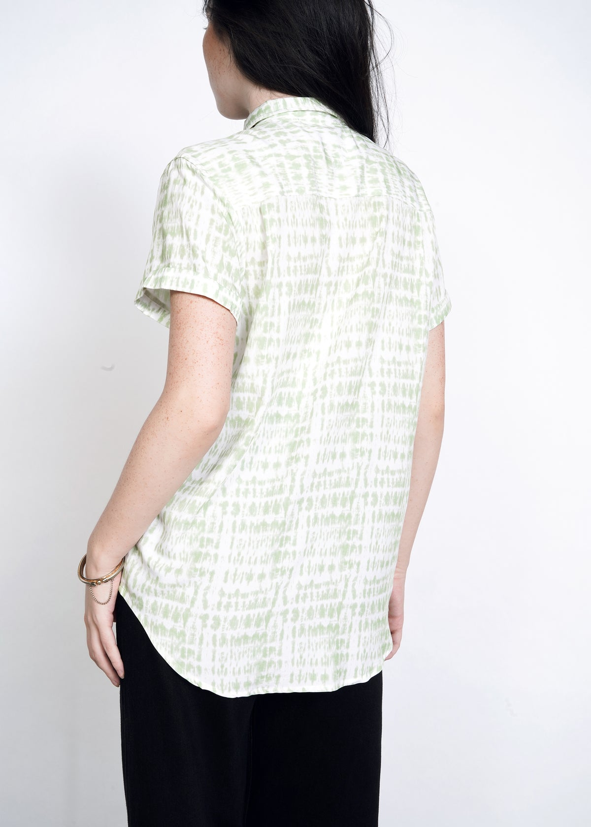 Back view of model wearing celadon green shabori print flowy button up