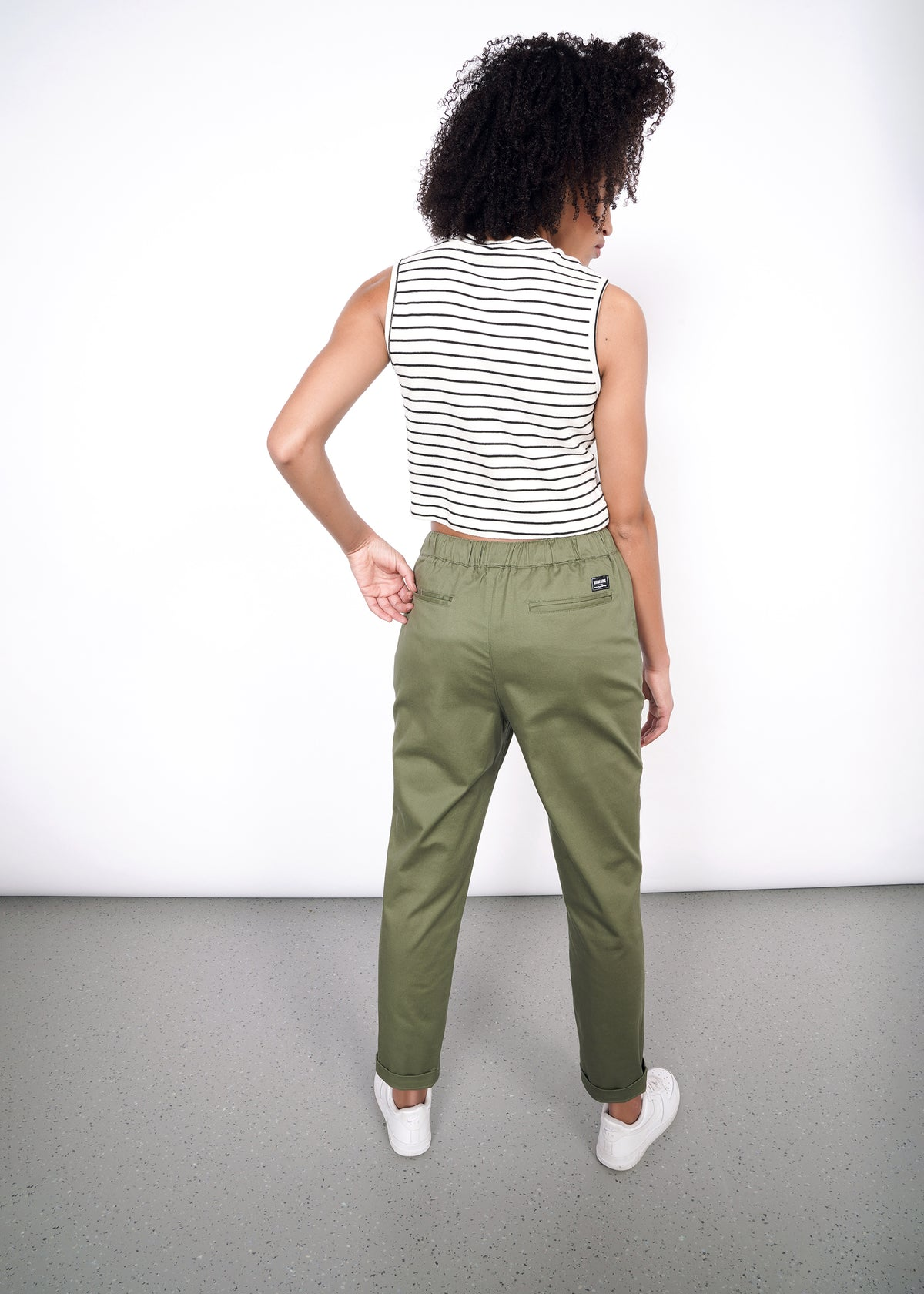 Model facing away from camera, showing back of the olive drawstring pants and two welted pockets