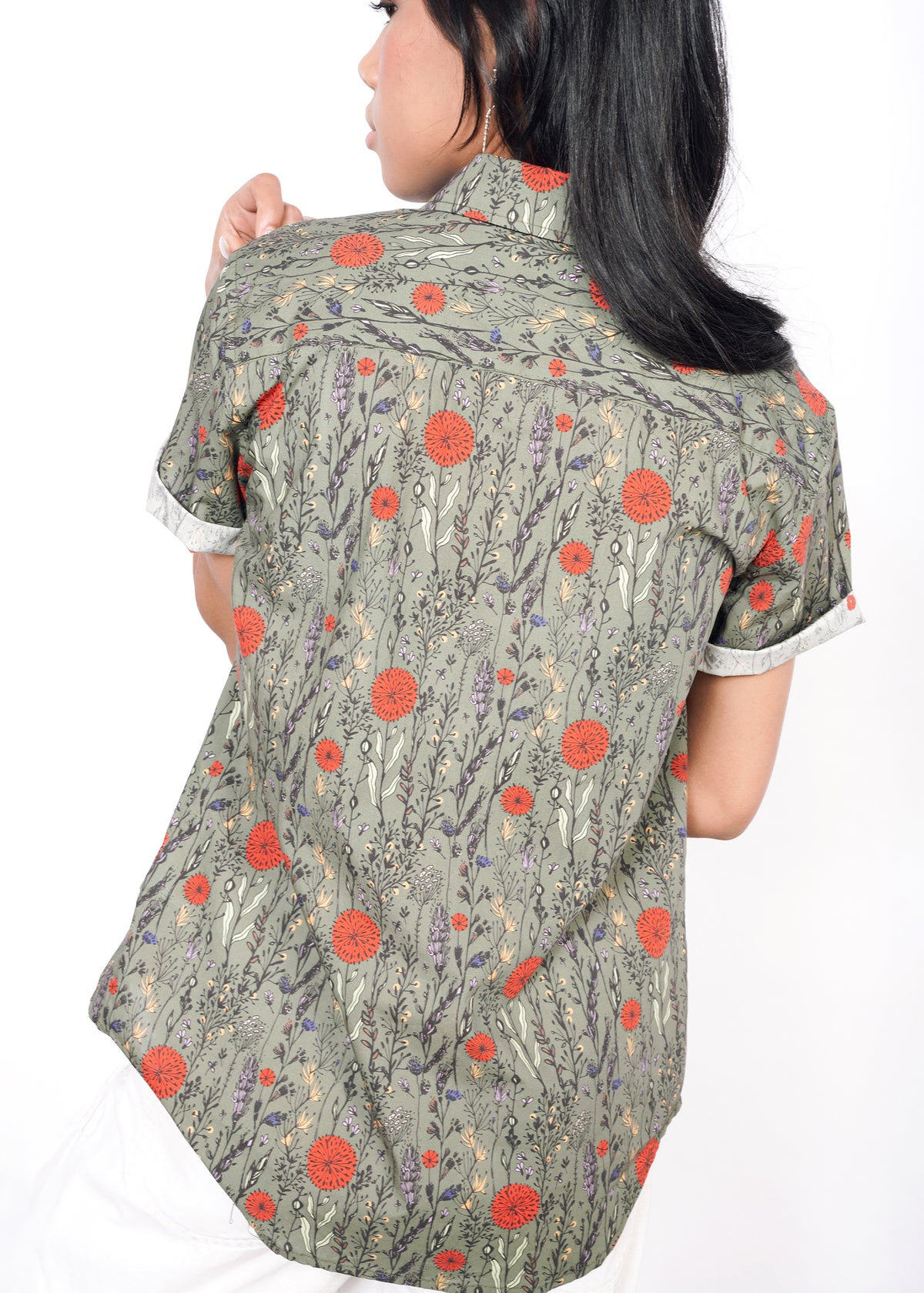 Backside of model wearing botanical all over printed short sleeved button up shirt in size XS, with the sleeves cuffed, untucked, with a curved hem