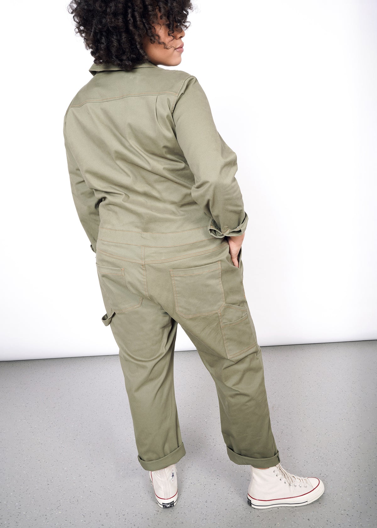 Model with back turned, wearing olive coveralls. Shows back pockets, hammer loop, and side leg pocket