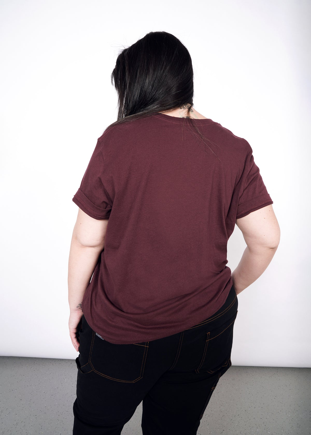 Back view of model wearing burgundy merlot graphic tee in size XXL, untucked, paired with black pants