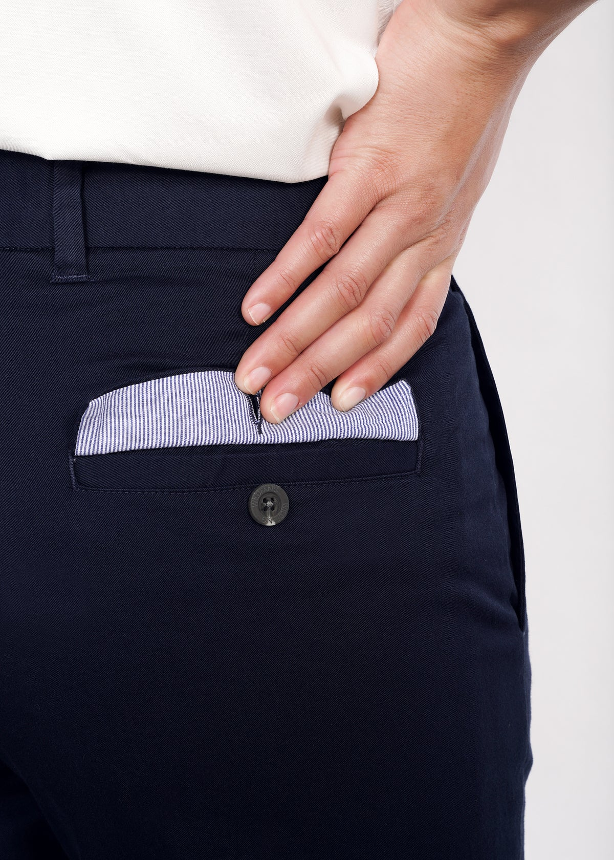 Hand holding open back pocket flap to show pinstripe interior lining and welted pocket with button, on navy trouser pants