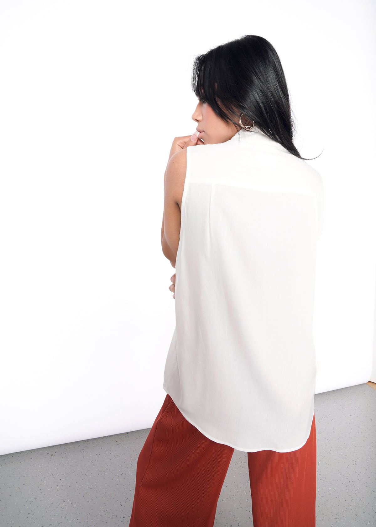 Backside of model wearing white sleeveless drapey button up shirt in size XS with a curved hem, with orange pants,