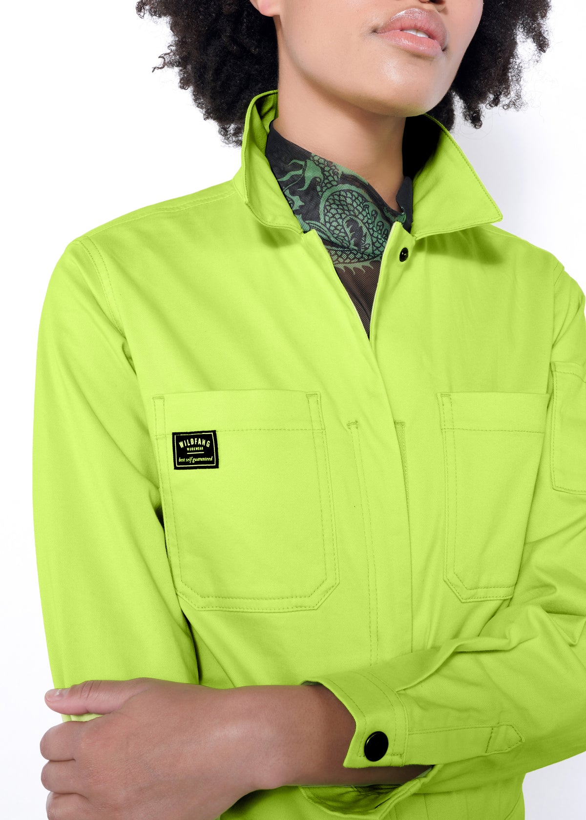 Model wearing neon green long sleeved essential coverall jumpsuit in size small, layered with green and black mesh top underneath and collar popped