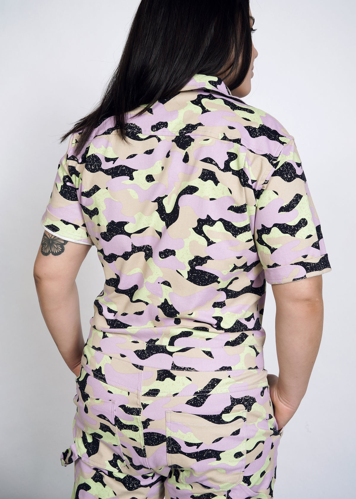Model with back turned wearing lavender, celadon, black, and tan camouflage all over print short sleeve coverall jumpsuit in size L, with hands in pockets