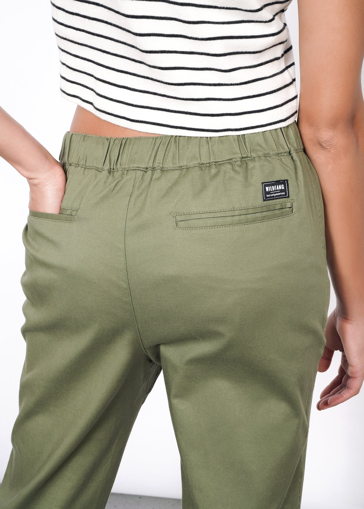 Hand in back pocket, closeup of back of olive drawstring pants, featuring patch