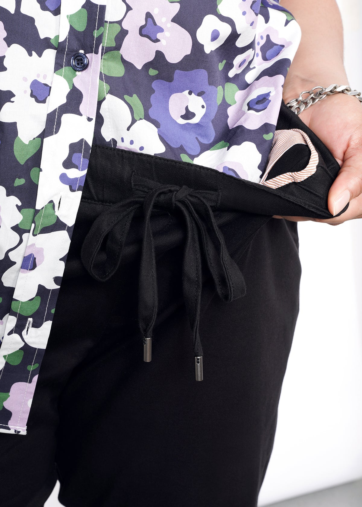 Detail shot of waistband and interior lining on black drawstring pant